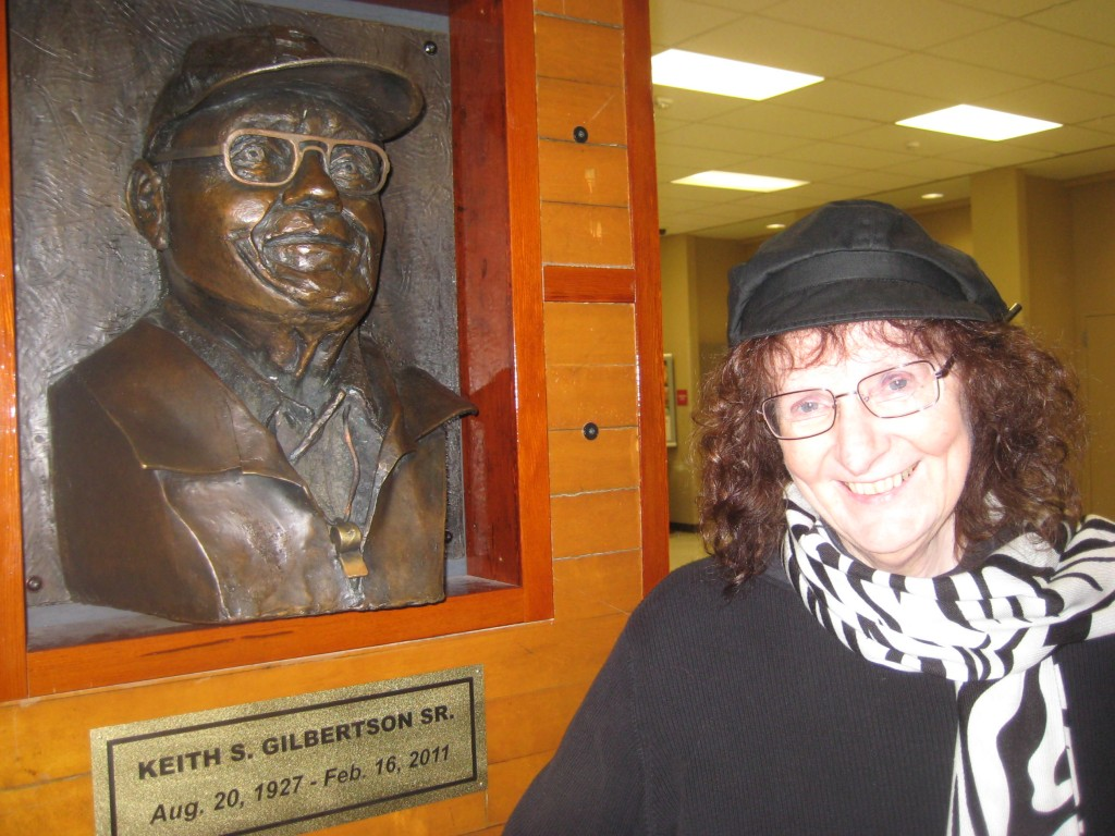 Sculptor Louise McDowell poses with the bronze bust she fashioned from a photograph of Keith Gilbertson Sr.  (Keith Olson photo)