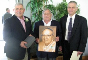 Keith Jr., Jim and Jay Gilbertson pose with their father's portrait at the WIAA Hall of Fame induction luncheon. (Keith Olson photo)